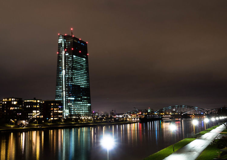 Scenic view of river by illuminated building in city at night