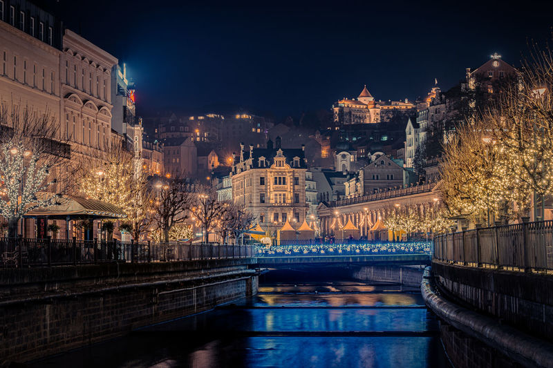 Illuminated bridge over river by buildings in city at night