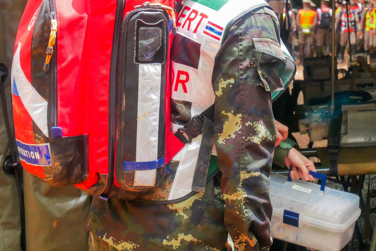 Midsection of army solider holding first aid kit outdoors