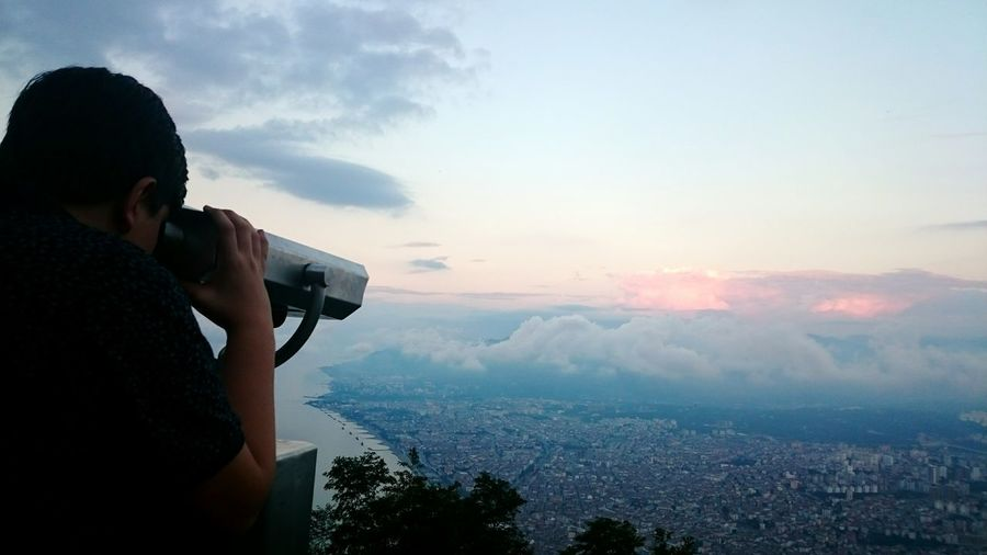Side view of boy looking through coin-operated binoculars against sky during sunset