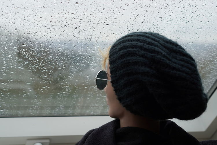 Portrait of woman looking through window during rainy season