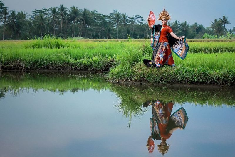 Reflection Of Female Model Standing In Traditional Clothing On Lake