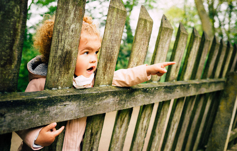Child Pointing By Wooden Fence