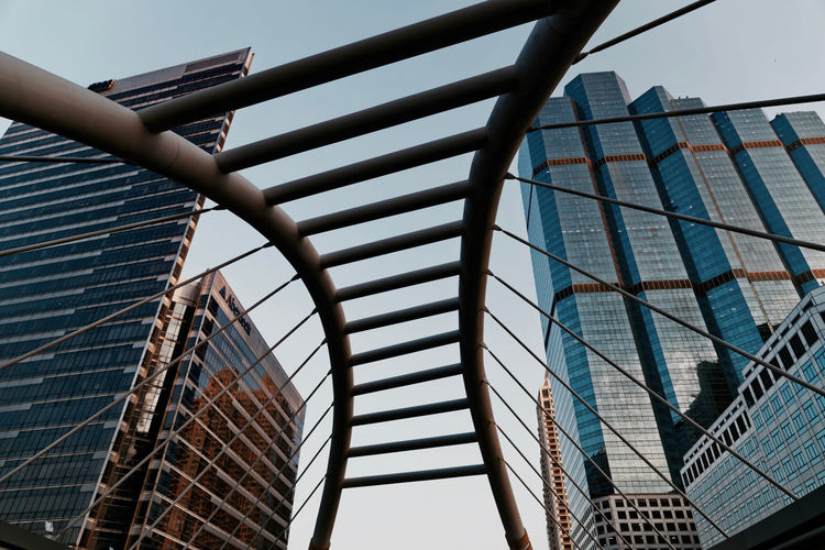 Low angle view of modern buildings against sky seen through bridge at sathon district