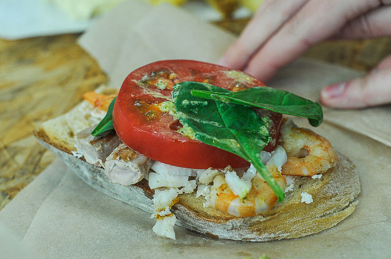 Cropped Image Of Hand By Open Faced Sandwich On Table