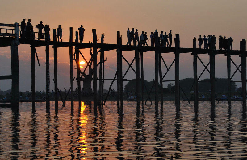 Silhouette of people walking on pier over lake