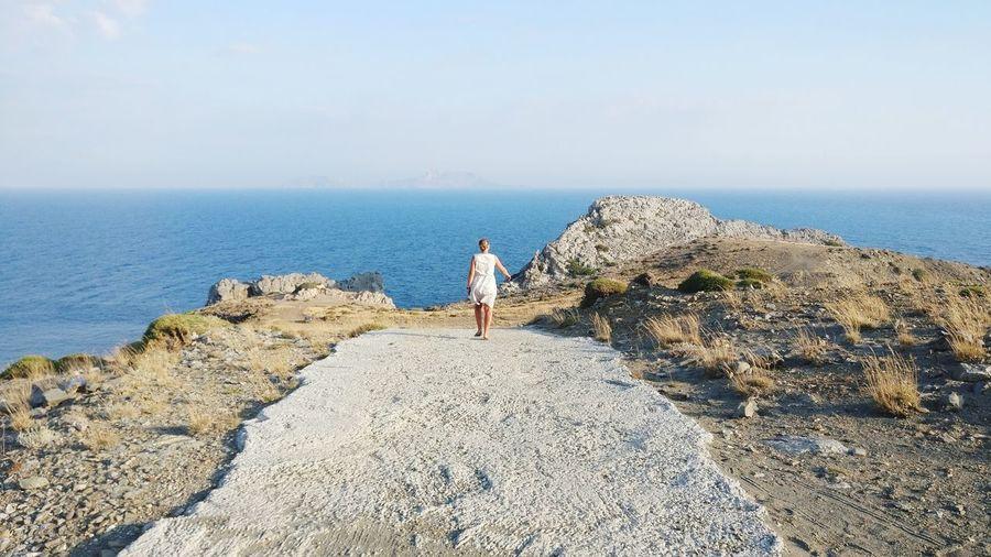 Rear view of woman walking towards sea against sky
