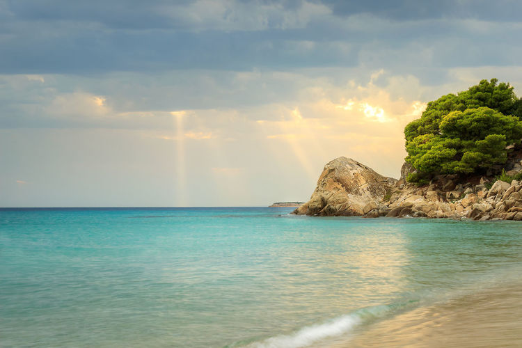 Sun rays passing through the clouds and falling on turquoise sea water of Koviou beach and beautiful rocks Seaside Orange Color Golden Hour Sunset Sky Travel Destination Landscape Seascape Vibrant Color Beach Long Exposure Turquoise Green Trees Foam Silky Reflective Blue Sun Rays Cloudy Murky Season  Summer Hollidays Stunning Saturated Color