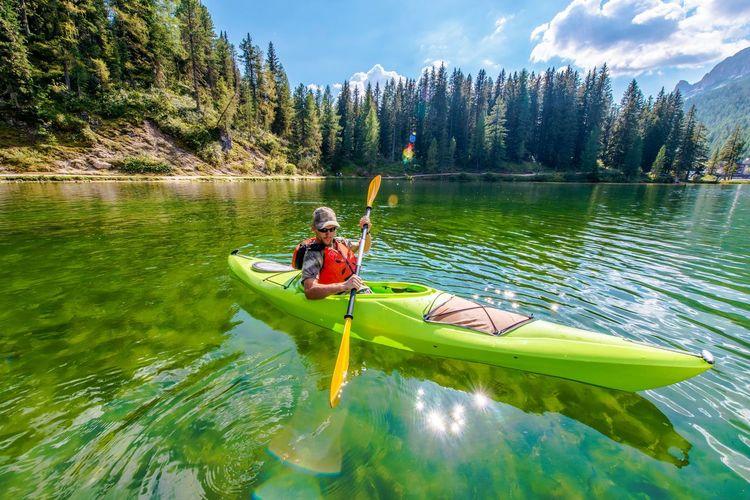 Mid Adult Man Kayaking On Lake Against Sky