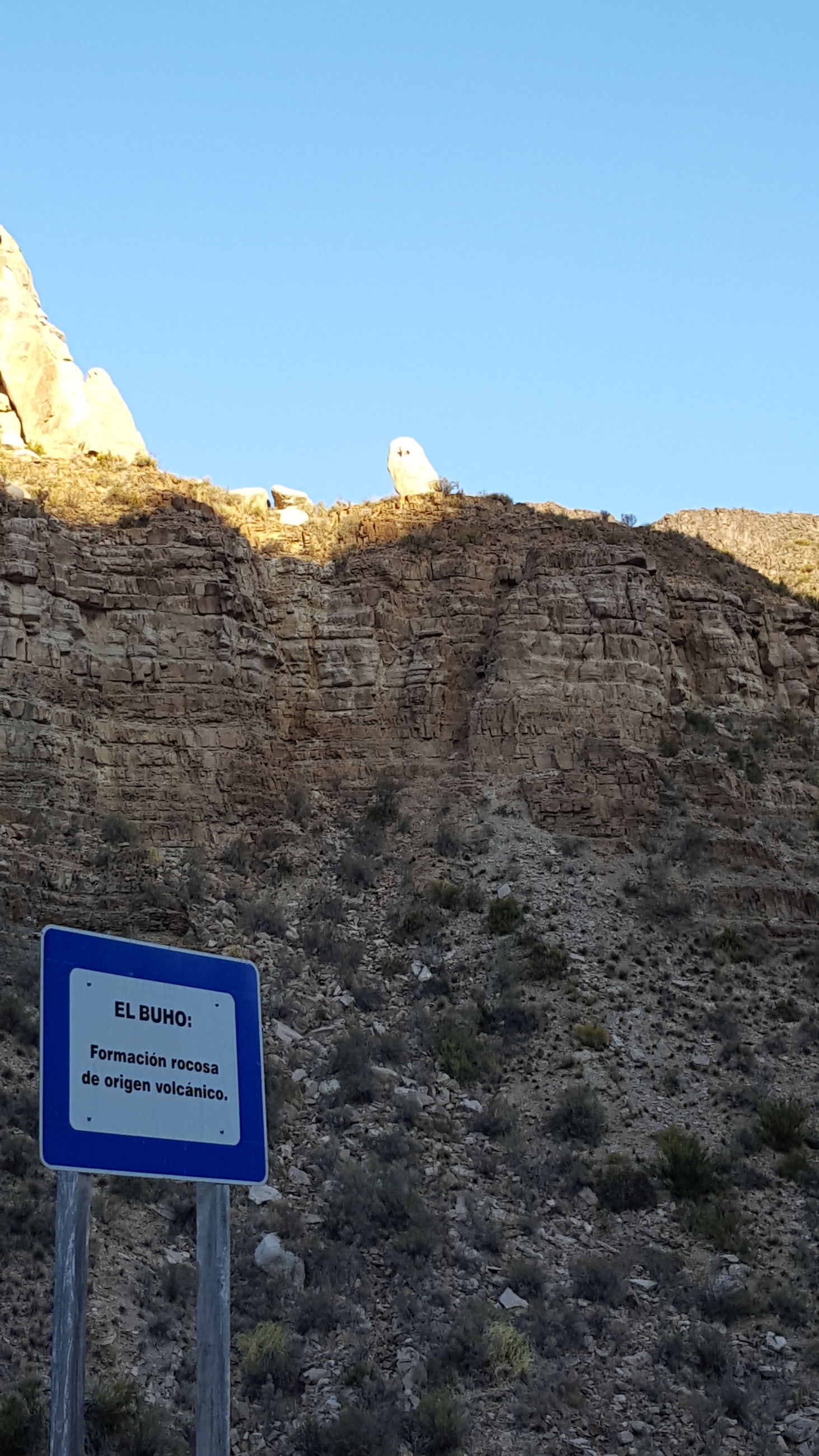 rock formation, blue, rock - object, geology, clear sky, low angle view, physical geography, day, text, communication, cliff, copy space, no people, outdoors, rocky mountains, mountain, nature, beauty in nature, tranquility, travel destinations, scenics, sky