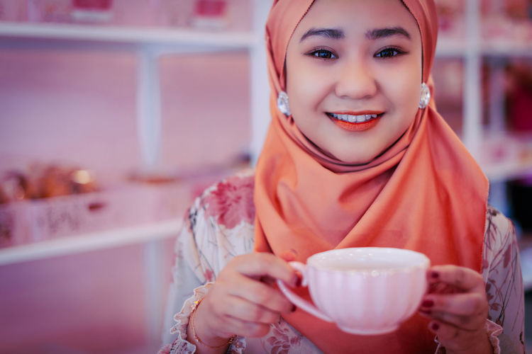 Portrait of a smiling young woman with coffee
