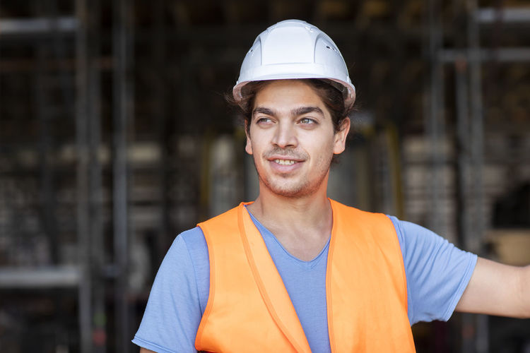 Portrait of smiling man standing at construction site