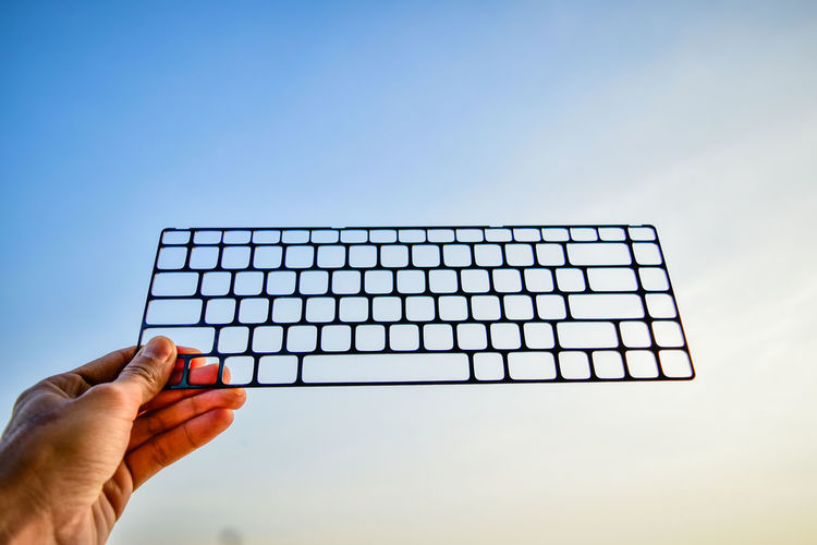 Cropped Hand Holding Keyboard Frame Against Sky