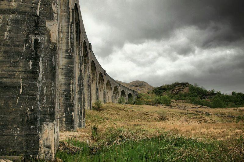 Railway Bridge By Field Against Cloudy Sky