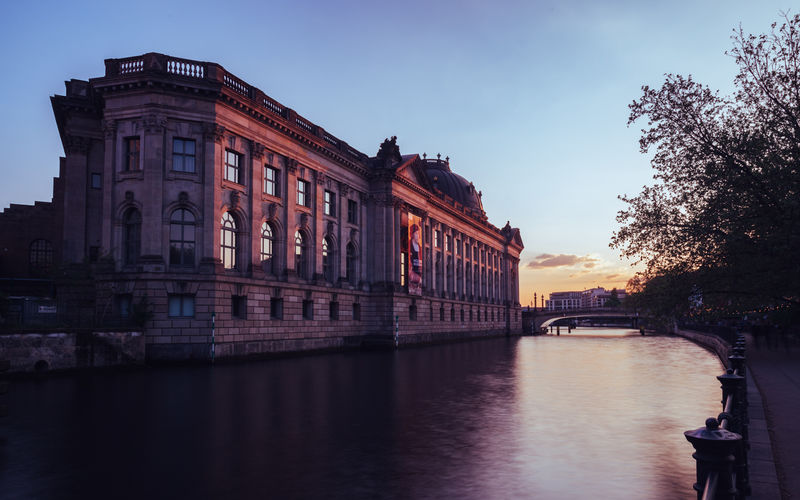 Historic building by spree river at sunset