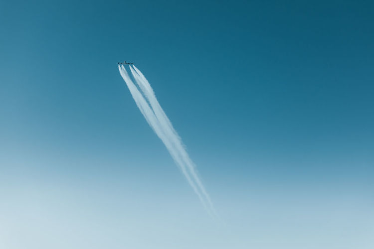 Low angle view of airplane flying with vapor trails in clear blue sky