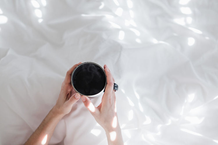 High angle view of person holding ice cream on bed