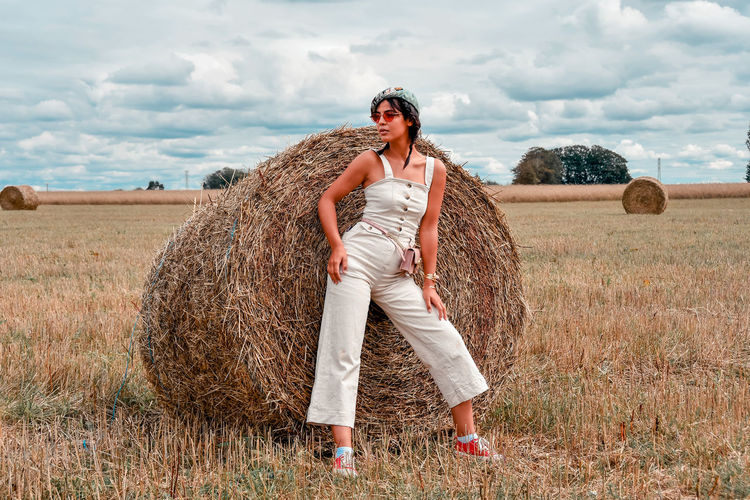 Full length of young woman standing by hay on field