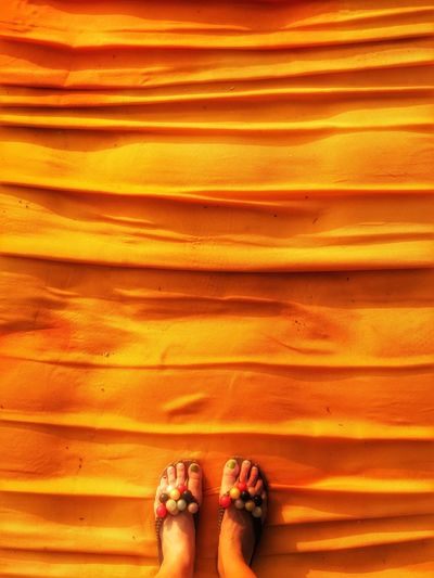 Low section of woman standing on orange carpet