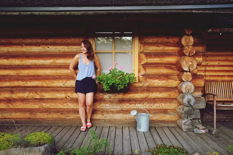 Full length of woman standing against log cabin