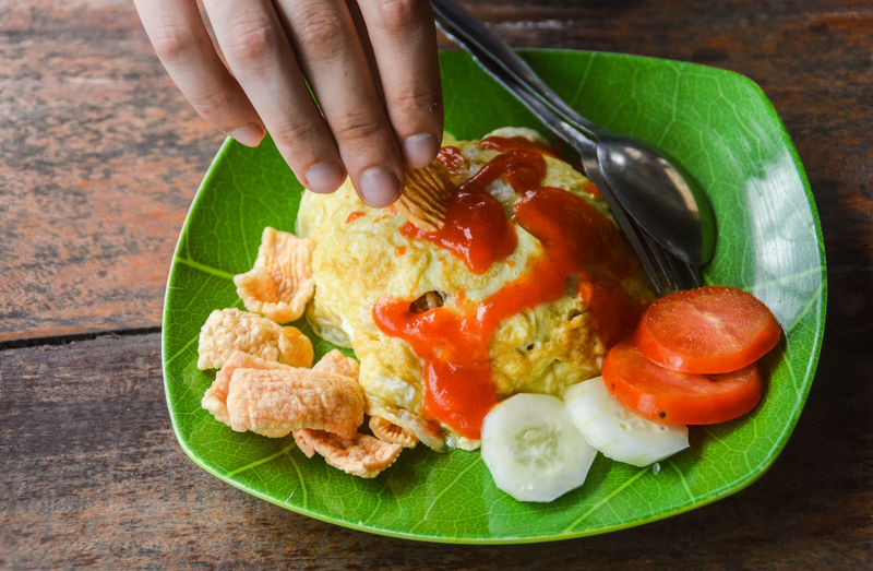 indonesian breakfast of nasi goreng topped with omelet Healthy Choice Summer Indonesian Breakfast Indonesian Food Nasi Goreng TELOR Travel Food And Travel Human Hand Human Body Part One Person People Food Plate Adult Healthy Eating Indoors  Ready-to-eat Freshness Close-up Day Food Stories