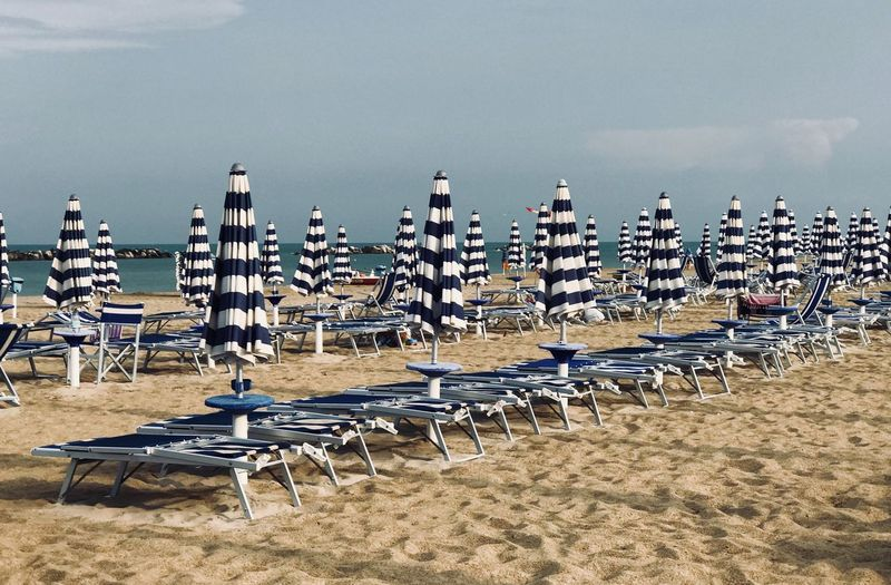White and blue beach umbrellas in a row Beach Umbrellas Beach Water Chair Beach Sky Nature Seat Land Large Group Of Objects In A Row Parasol Sand Absence Sea 17.62°