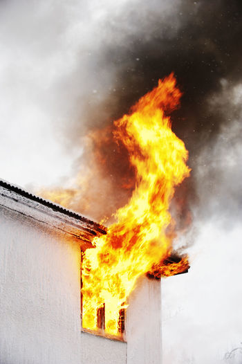 Low angle view of fire on building against sky