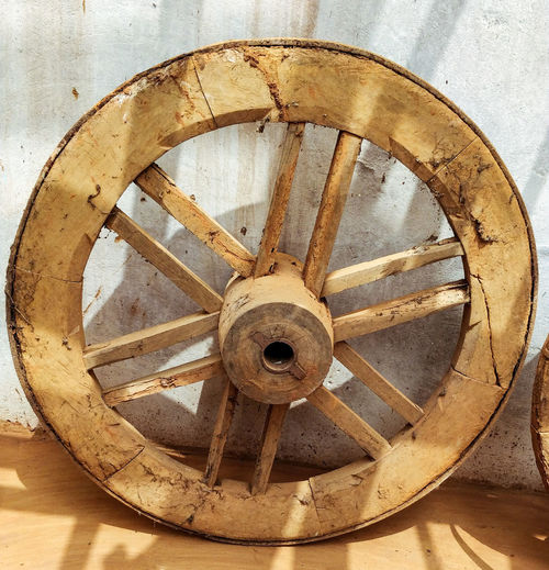Close-up of rusty wheel against wall