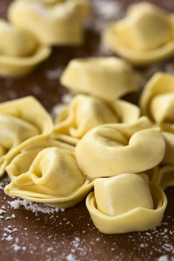 Raw cheese filled tortellini pasta on floured surface, photographed with natural light (Selective Focus, Focus one third into the image) Cooking Filled Raw Stuffed Vegetarian Vegetarian Food Close Up Close-up Dried Dry Food Food And Drink Ingredient Italian Italian Food Pasta Raw Food Tortellini  Tortelloni  Traditional Uncooked Uncooked Pasta Vertical