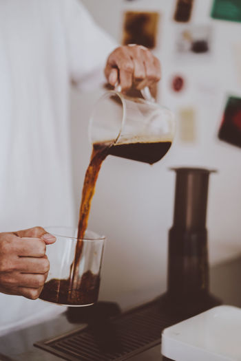 barista pour coffee into glass after brewing coffee, home brewing style, dark tone Bar Barista Beverage Black Brew Brown Cafe Coffee Drink Fresh Glass Hand Hot Lifestyle Man Plastic Pour Practise Prepare Press Professional Relax Selective Focus Serve Water White Work