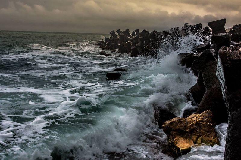 Waves breaking on rocks against sea