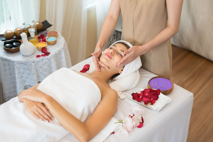 Midsection Of Masseur Massaging Young Woman On Table In Spa