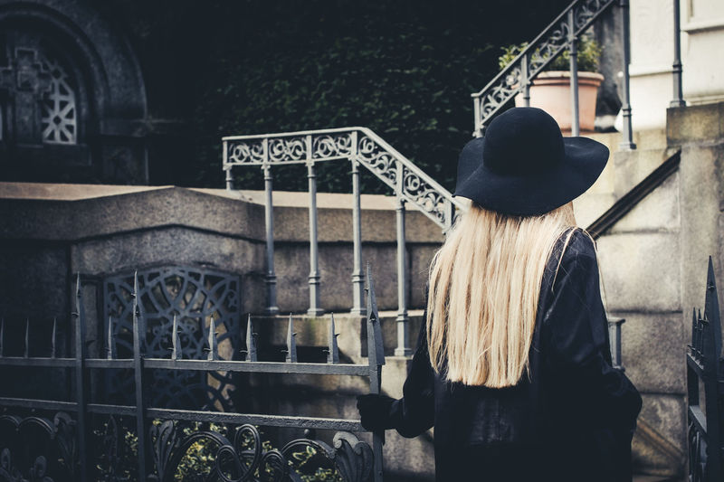 Rear View Of Woman With Long Blond Hair Entering From Gate In Yard