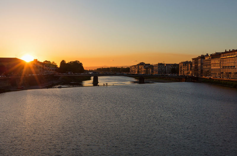 Scenic view of river by buildings against sky during sunset