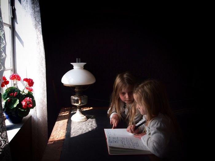 High angle view of siblings doing homework