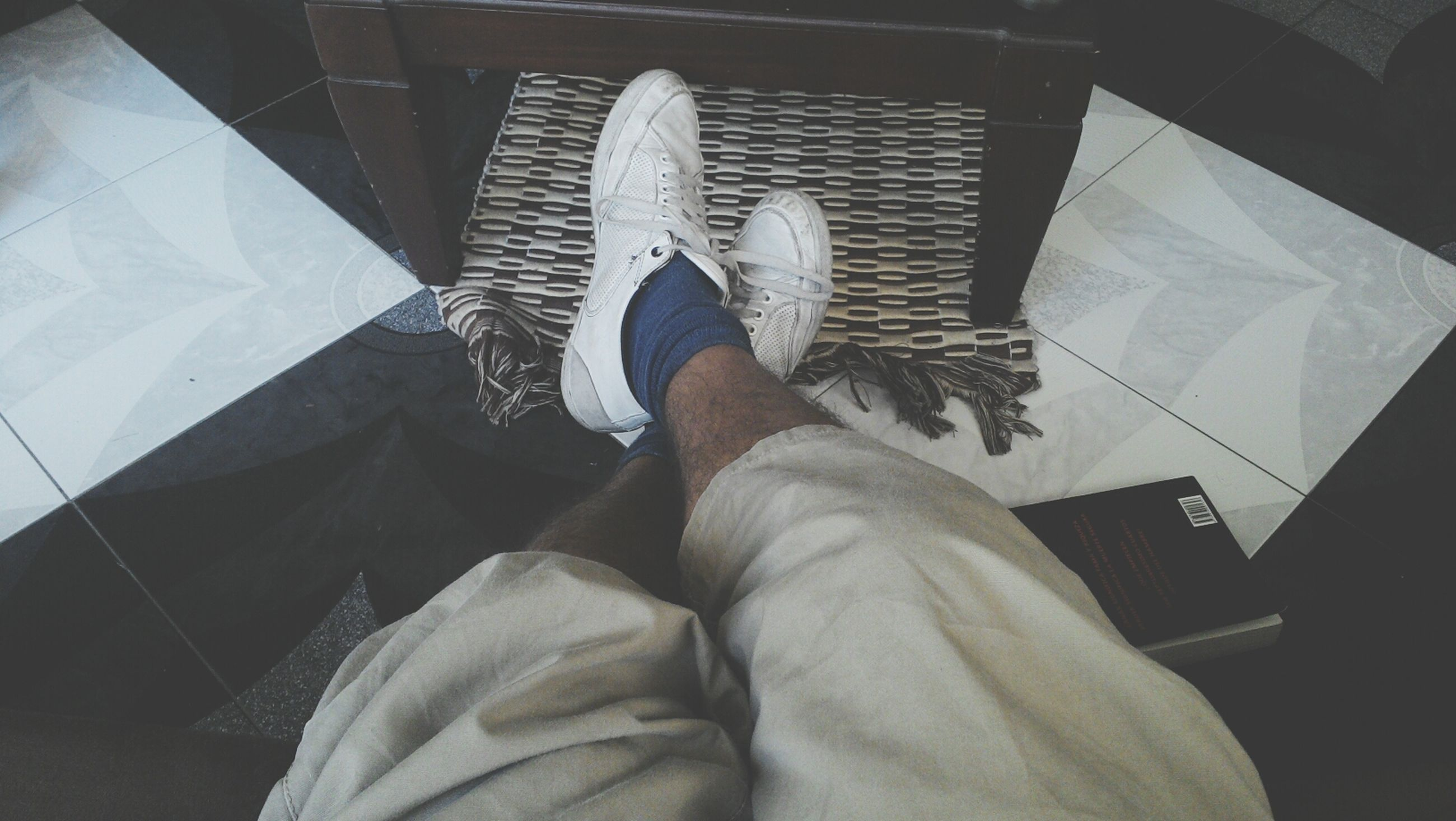 indoors, low section, person, personal perspective, lifestyles, men, sitting, relaxation, leisure activity, high angle view, human foot, unrecognizable person, part of, home interior, shoe