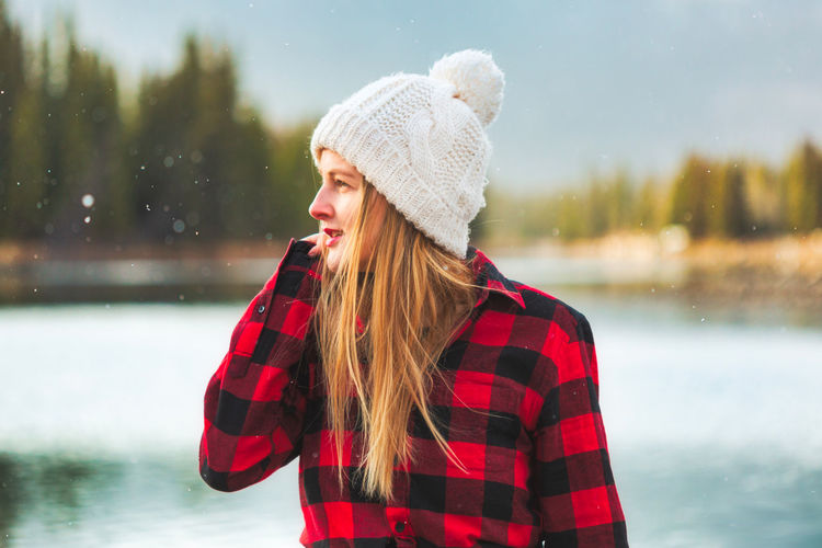 Smiling woman looking away while standing by lake during winter