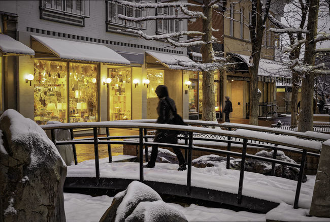 A woman crosses a snowy bridge in a shopping district on a snowy evening. Architecture Bridge City Cold Temperature Evening Lighted Lights One Woman Outdoors People Shopping Snow Storefront Urban Walking Welcoming Winter Snowing