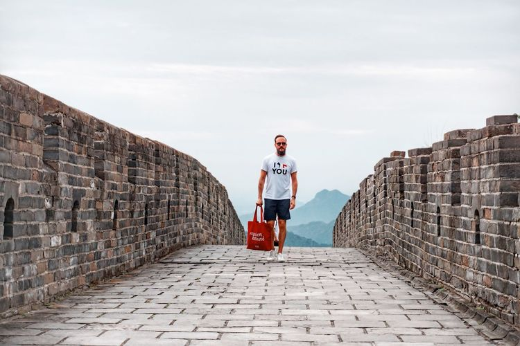 Full Length One Person Lifestyles Sky Real People Architecture Leisure Activity Young Adult Standing Adult Outdoors Day Front View Wall Built Structure Casual Clothing Nature Men Stone Wall