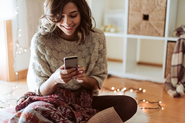 Smiling young woman using mobile phone