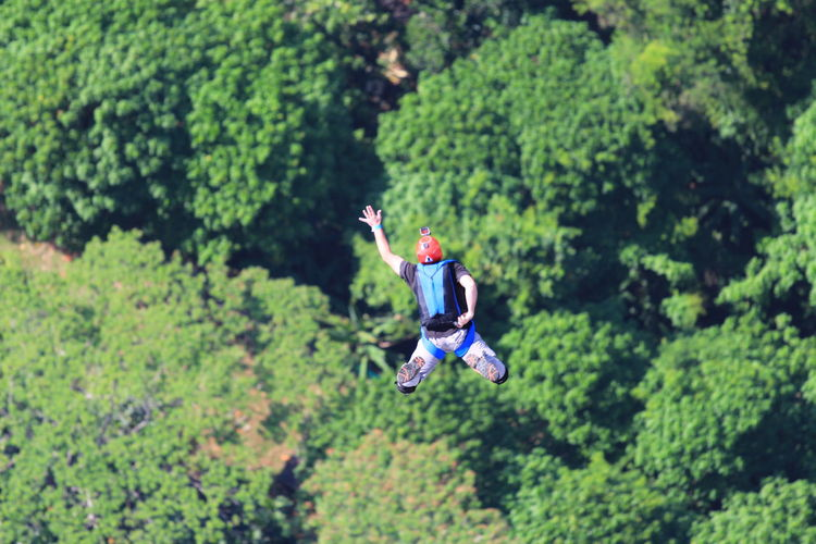 High Angle View Of Man Base Jumping With Arms Raised Against Trees
