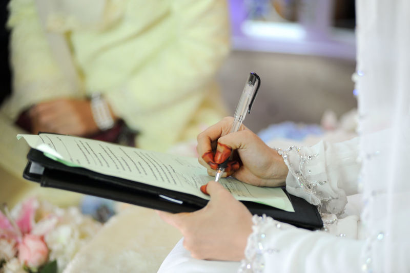 Midsection of bride signing marriage certificate