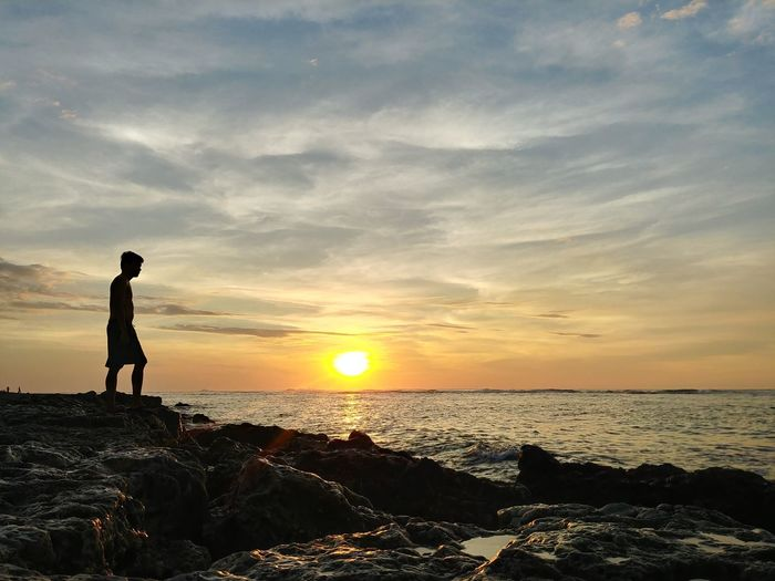 Silhouette man standing on rock at shore against sky during sunset