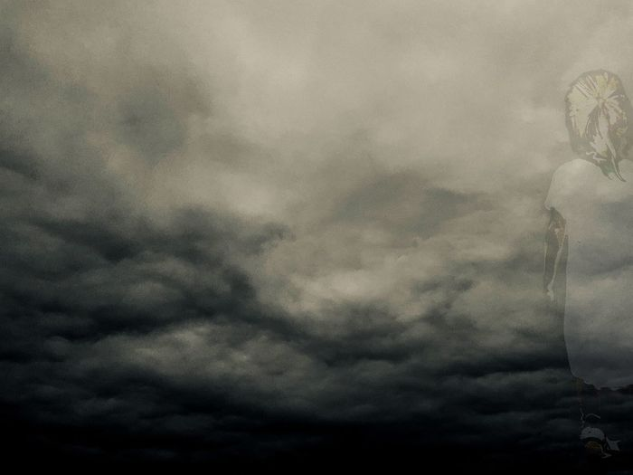 Low angle view of statue against storm clouds