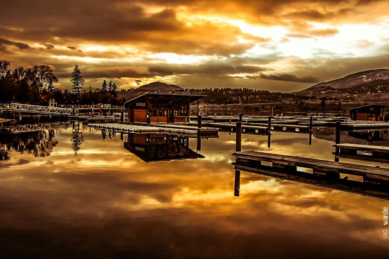 cloud - sky, reflection, sky, sunset, water, built structure, dramatic sky, orange color, architecture, nature, waterfront, outdoors, beauty in nature, scenics, building exterior, transportation, no people, mountain, day
