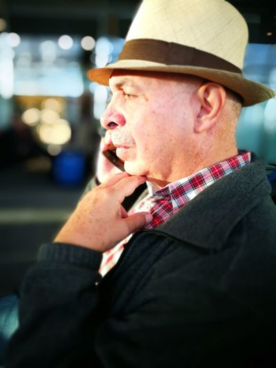 Side view of man wearing hat talking on mobile phone