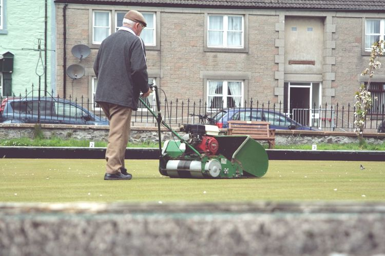 Man working on bowling green mowing the grass