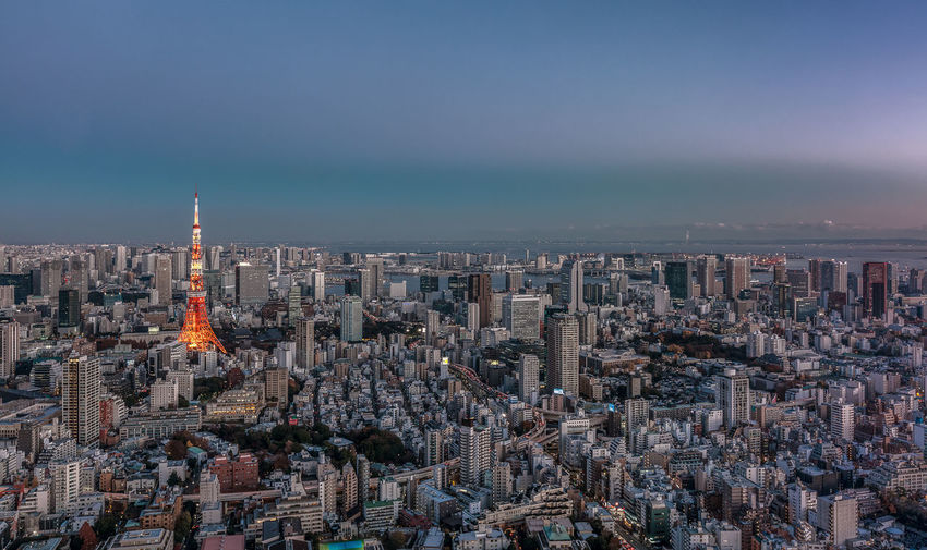 tokyo tower rises up above a vibrant tokyo city Aeriel Shot Blue Hour Cityscape Tokyo,Japan Architecture Building Building Exterior Built Structure City Cityscape Crowd Crowded Dusk Financial District  High Angle View Landscape Nature Office Building Exterior Outdoors Residential District Roppongi Hills Sky Skyscraper Spire  Sunset Tower Toyko Tower Travel Destinations Urban Skyline