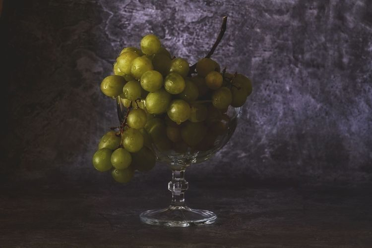 Close-up of grapes in glass container on table
