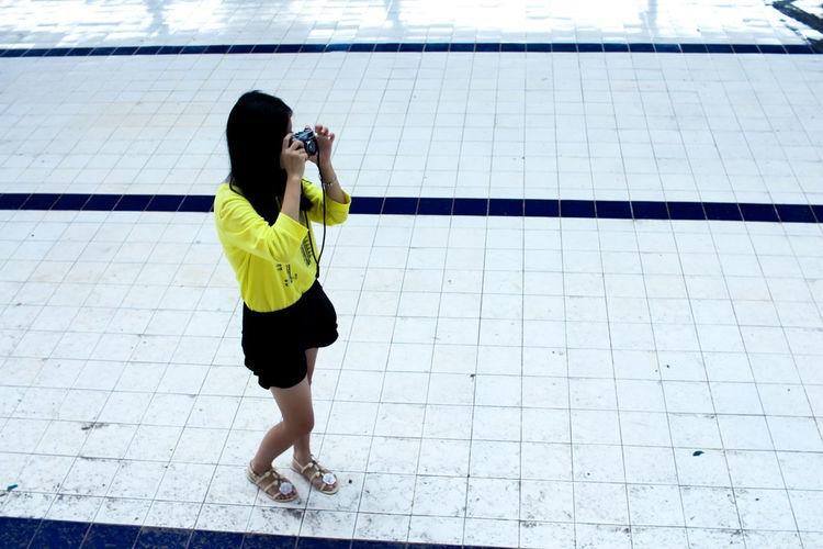 Full length rear view of woman walking in swimming pool